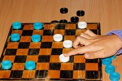 Handflickan flyttar kontrollörer på schackbrädet Royaltyfri Fotografi