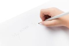 Handflickan skriver hans namn vid blyertspennan Royaltyfria Bilder