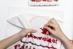 Handflickor broderar modellen genom att använda ramen Royaltyfri Foto