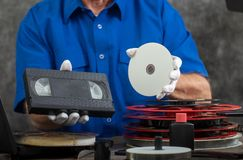 Handfotograf som rymmer VHS bandet och DVD-disketten för omvandling arkivfoton
