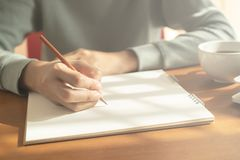 Handfrau, die Notizbuch schreibt hölzerner Schreibtischhintergrund haben Kaffeetasse und Laptop im Morgenlicht stockfoto