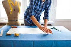 Handfrau Schneider, der eine Rolle auf der schneiden des Gewebes sie arbeitet Stockbilder
