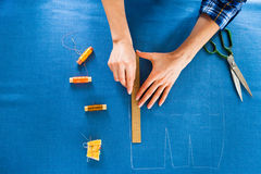 Handfrau Schneider, der eine Rolle auf der schneiden des Gewebes sie arbeitet Stockbild