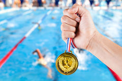 Handful of asian man holding gold medal with blurry background. Handful of asian man holding gold medal with blurry background of swimming pool Stock Photos