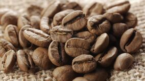 A handful of brown, roasted coffee beans on burlap sacking background, close up, rotation. A handful of brown, roasted coffee beans on burlap sacking background stock footage