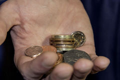 Handful of Change. An image of a hand holding a few different coins Stock Photo