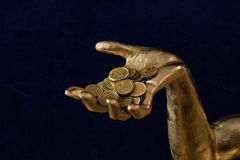 A handful of coins in gold-plated hand.  Stock Photography
