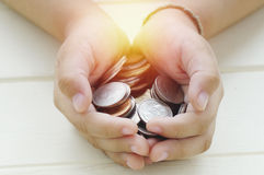 Handful of coins in palm hands Stock Image