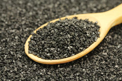 A handful of crushed coal in a wooden spoon Royalty Free Stock Photography