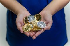 Handful of crypto currencies. A young girl with a bunch of crypto currency coins cupped in both hands Royalty Free Stock Photo