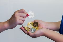 Handful of crypto currencies. A young girl with a bunch of crypto currency coins cupped in both hands receiving an additional coin Stock Photos