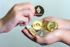 Handful of crypto currencies. A young girl with a bunch of crypto currency coins cupped in both hands receiving an additional coin Royalty Free Stock Images