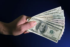 Handful of dollars. Hand holding dollars, $100, $50, $20,and $10 royalty free stock photography