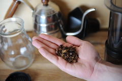 A handful of dried coffee berries cascara on the palm. Drip Coffee Maker, glass jug server in the background. On wooden texture stock image
