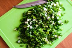 Ð¡hopped green onions on the kitchen board royalty free stock photo
