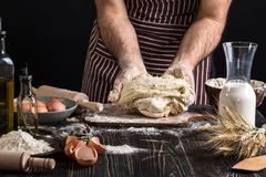 Against the background of men`s hands knead the dough. Ingredients for cooking flour products or dough bread, muffins Stock Images