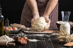 Against the background of men`s hands knead the dough. Ingredients for cooking flour products or dough bread, muffins Stock Photos