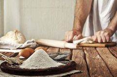 A handful of flour on a rustic kitchen. Against the background of men's hands knead the dough. Ingredients for cooking flour products or dough (bread, muffins stock photo