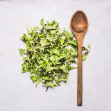 Handful fresh salad Lollo rosso with a wooden spoon,  wooden rustic background top view close up Stock Photos