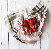 Handful of fresh strawberries is on white wooden table Stock Image