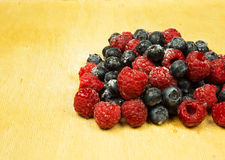 A handful of frosted highbush blueberries and raspberries on old Royalty Free Stock Images