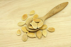 Handful of gold pumpkin seeds in a wooden spoon Royalty Free Stock Photography