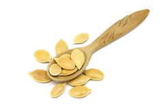 Handful of gold pumpkin seeds in a wooden spoon Royalty Free Stock Image