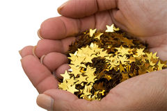 Handful Of Gold Stars. Two hands holding lots of gold stars on a white background, handful of gold stars Royalty Free Stock Images