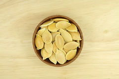 A handful of golden pumpkin seeds in a wooden cup Stock Photo