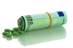 Handful of green pills and euro. Handful of green pills with a euro banknot-roll Royalty Free Stock Photo