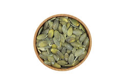 Handful of green pumpkin seeds in a wooden bowl Royalty Free Stock Photography