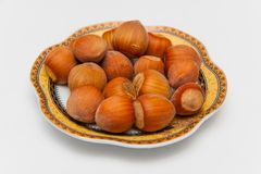 A handful of hazelnuts on a plate. The seeds are covered in wooden shells of light brown color. The plate is white with decorated motifs on the rim. The Royalty Free Stock Image