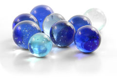 Handful of Marbles. A handful of blue glass marbles on a white surface Royalty Free Stock Photos