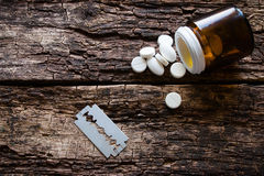 Handful of pills and blade for suicide on a wooden Royalty Free Stock Photos