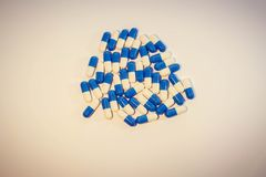 A handful of pills. Capsules medications white and blue medicament stock photos