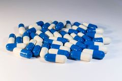 A handful of pills. Capsules medications white and blue. Neer royalty free stock image