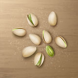 Handful of pistachio nuts. Vector realistic handful of whole and cracked pistachio nuts with salt top view isolated on wooden table Royalty Free Stock Photos
