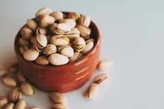 Handful of pistachios in a brown vase stock photos