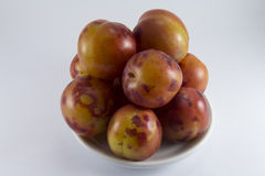 Handful of plums on a white porcelain dish Stock Image