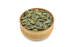 A handful of pumpkin seeds in a wooden bowl Royalty Free Stock Photos
