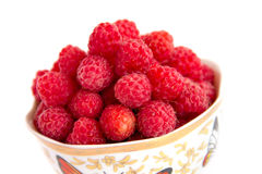 A handful of raspberries in a bowl. A juicy berry of raspberries in a vase. A photo in a light key Royalty Free Stock Image