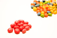 A handful of red candies in the foreground Royalty Free Stock Photo