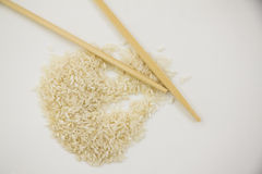 Handful of rice on white with chopsticks Royalty Free Stock Image