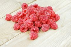 Handful of ripe raspberries on the background of a board made of natural wood Royalty Free Stock Photo