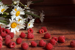 Handful of ripe raspberries and chamomile flowers on a wooden board Royalty Free Stock Photos