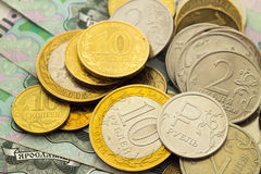 A handful of Russian coins of different denominations. Against the background of one thousand bills Stock Photos