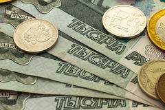 A handful of Russian coins of different denominations. Against the background of one thousand bills Royalty Free Stock Images