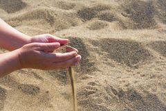 Handful of sand falling through the woman`s fingers, outdoor stock photos