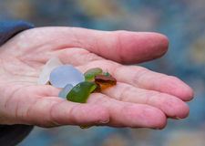 A handful of sea glass. A handful of gray, green, white and red sea glass or beach glass royalty free stock images