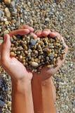 A handful of sea pebbles in women`s hands stock photos